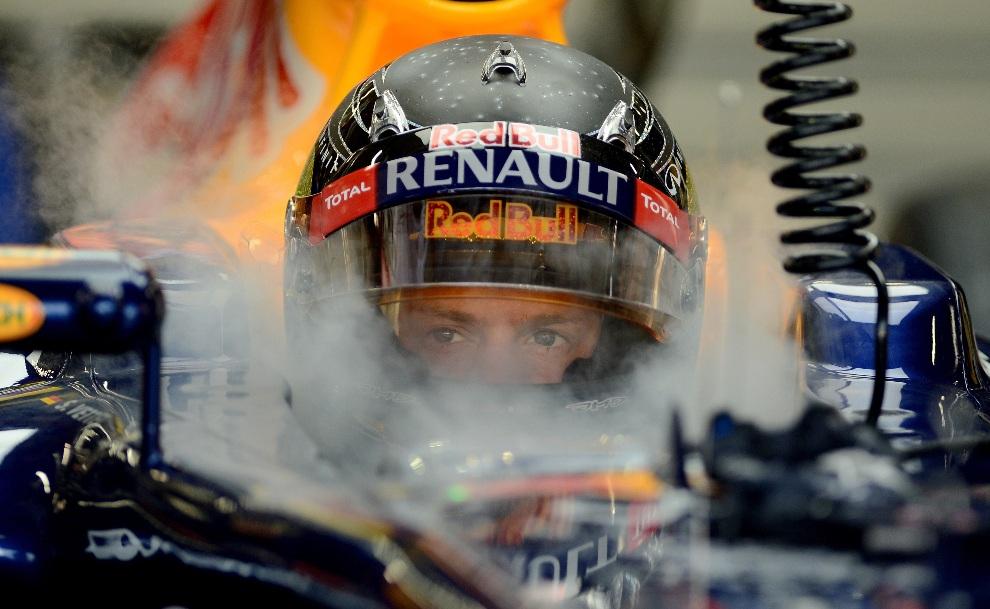 1.SINGAPUR, 21 września 2012: Kierowca zespołu Red Bull Renault,  Sebastian Vettel, za kierownicą bolidu w alei serwisowej. AFP PHOTO / Punit PARANJPE