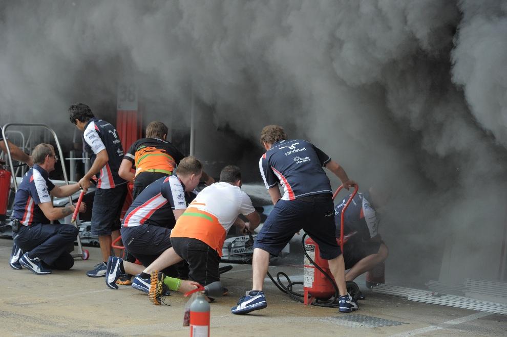 2.HISZPANIA, Montmeló, 13 maja 2012: Członkowie ekipy Williams gaszą pożar w alei serwisowej. AFP PHOTO / JOSEP LAGO