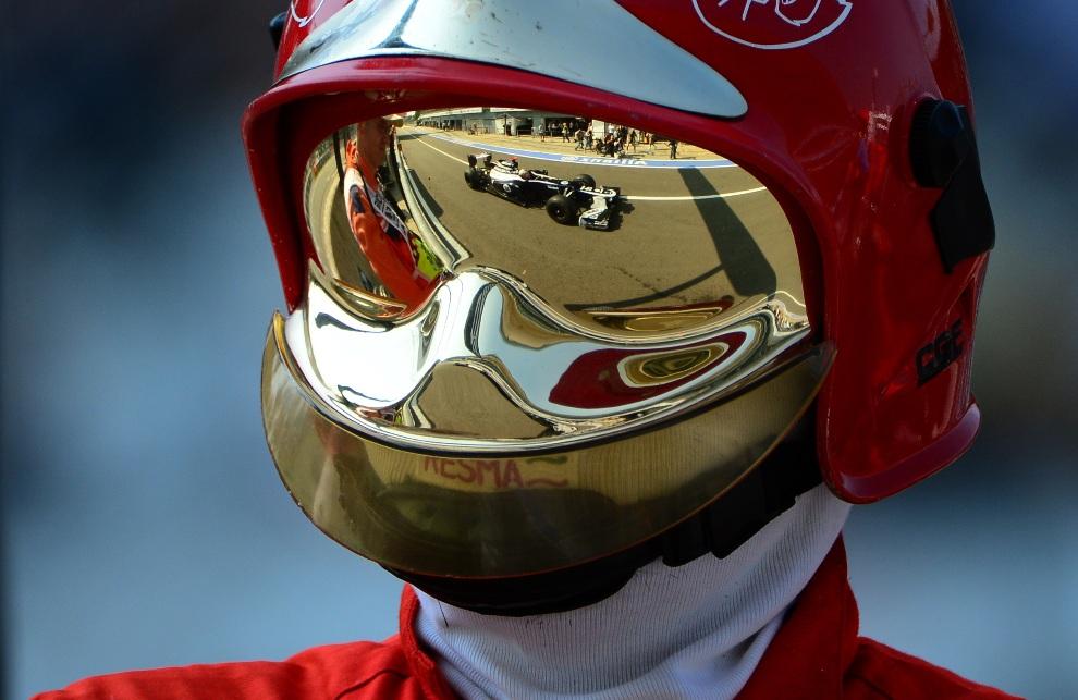 5.WŁOCHY, Monza, 7 września 2012: Bolid prowadzony przez  Pastora Maldonado odbija się w goglach strażaka. AFP PHOTO / OLIVIER MORIN