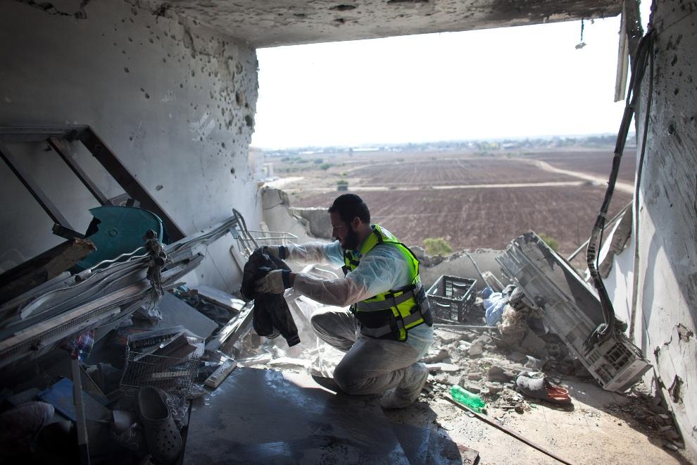 3.IZRAEL, Kirjat Mal'achi, 15 listopada 2012: Mężczyzna sprząta mieszkanie uszkodzone przez rakietę wystrzeloną przez Palestyńczyków. (Foto: Uriel Sinai/Getty   Images)