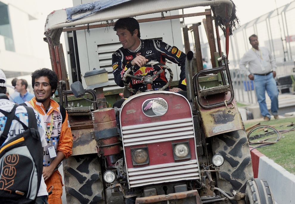 8.INDIE, New Delhi, 25 października 2012: Mark Webber za kierownicą ciągnika na torze Buddh International. AFP PHOTO/ MANAN VATSYAYANA