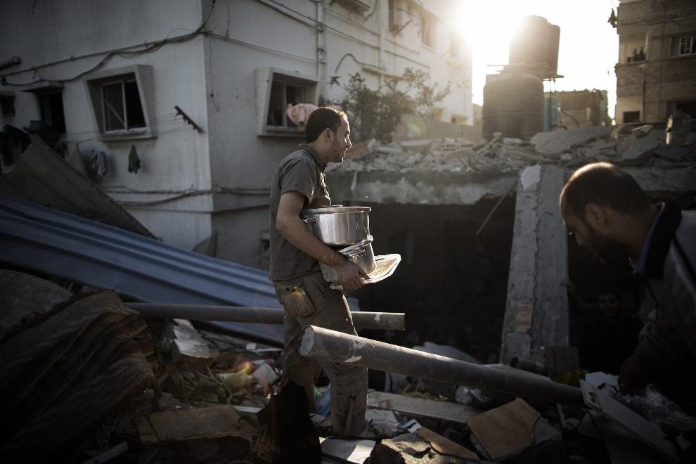 4.STREFA GAZY, Bajt Lahija, 18 listopada 2012: Mężczyzna zbiera sprzęty z gruzów zbombardowanego domu. AFP PHOTO/MARCO LONGARI