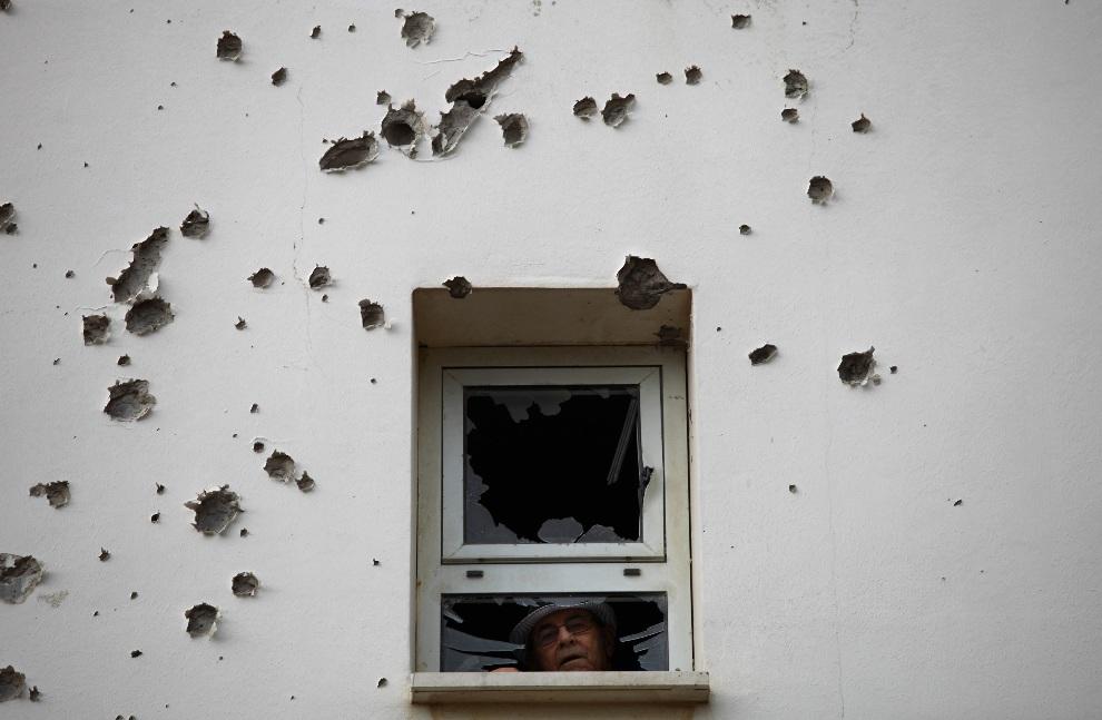 5.IZRAEL, Aszkelon, 18 listopada 2012: Mężczyzna w oknie ostrzelanego budynku mieszkalnego. EPA/ABIR SULTAN Dostawca: PAP/EPA.