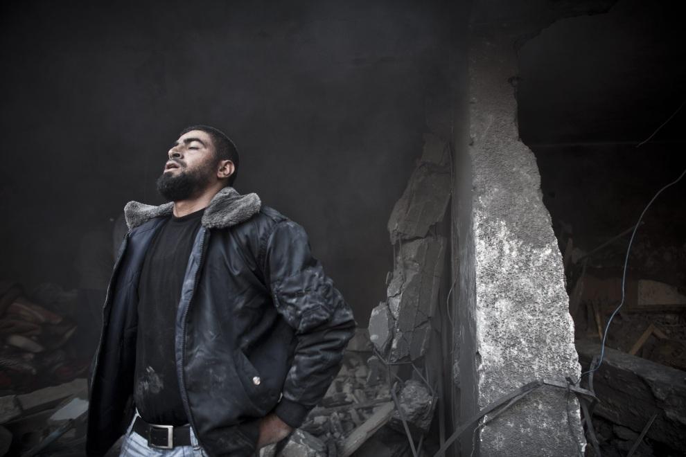 6.STREFA GAZY, 18 listopada 2012: Mężczyzna szukający ofiar nalotu w gruzach budynków. EPA/OLIVER WEIKEN Dostawca: PAP/EPA.