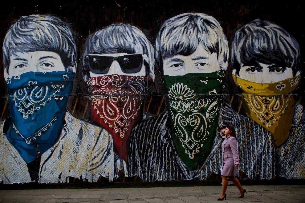 7.WIELKA BRYTANIA, Londyn, 8 listopada 2012: Kobieta mija mural przedstawiający zamaskowanych członków zespołu The Beatles. AFP PHOTO / ANDREW COWIE