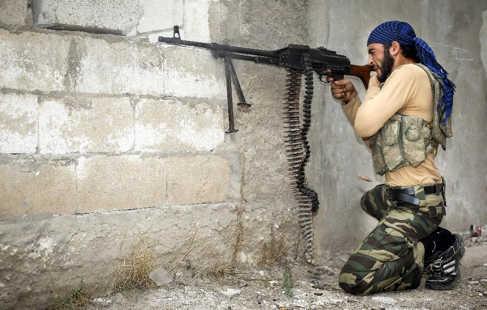 7.SYRIA, Harem, 31 października 2012: Rebeliant ostrzeliwuje pozycje wojsk rządowych. AFP PHOTO/JOHN CANTLIE