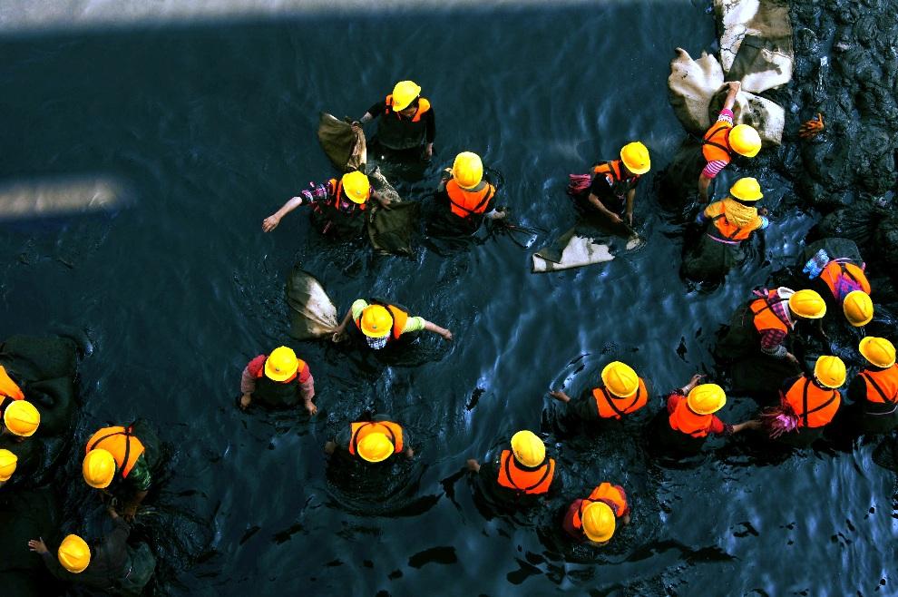 8.CHINY, Guiyang, 27 listopada 2012: Ekipa ratowników oczyszcza zatrute wody rzeki Nanming. AFP PHOTO