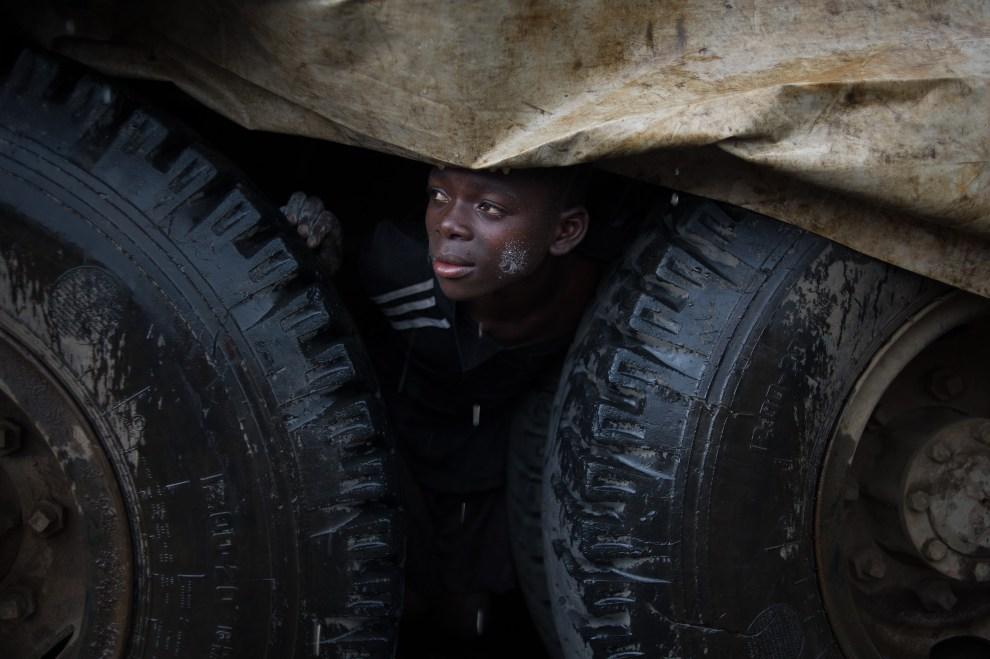 10.REPUBLIKA KONGA, Mungunga (obóz dla uchodźców), 2 grudnia 2012: Chłopiec chroni się pod ciężarówką przed ulewnym deszczem. AFP PHOTO/PHIL MOORE