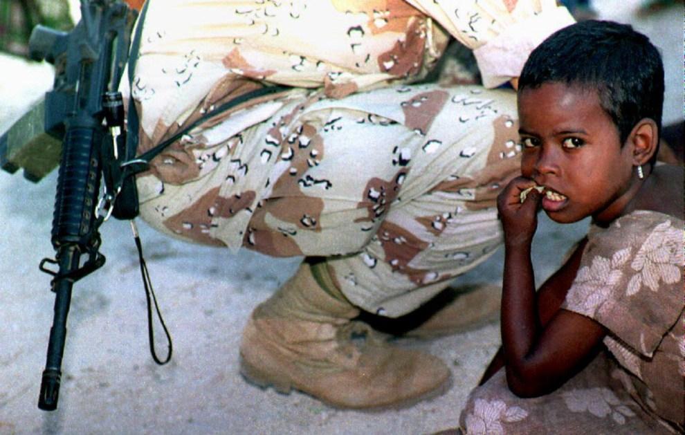11.SOMALIA, Mogadiszu, 23 lutego 1993: Somalijska dziewczynka obok klęczącego żołnierza. AFP PHOTO