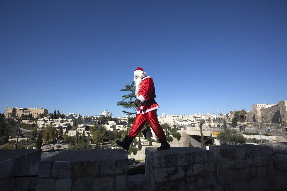 13.IZRAEL, Jerozolima, 23 grudnia 2012: Palestyńczyk w stroju Mikołaja na murze okalającym Stare Miasto. AFP PHOTO/MENAHEM KAHANA