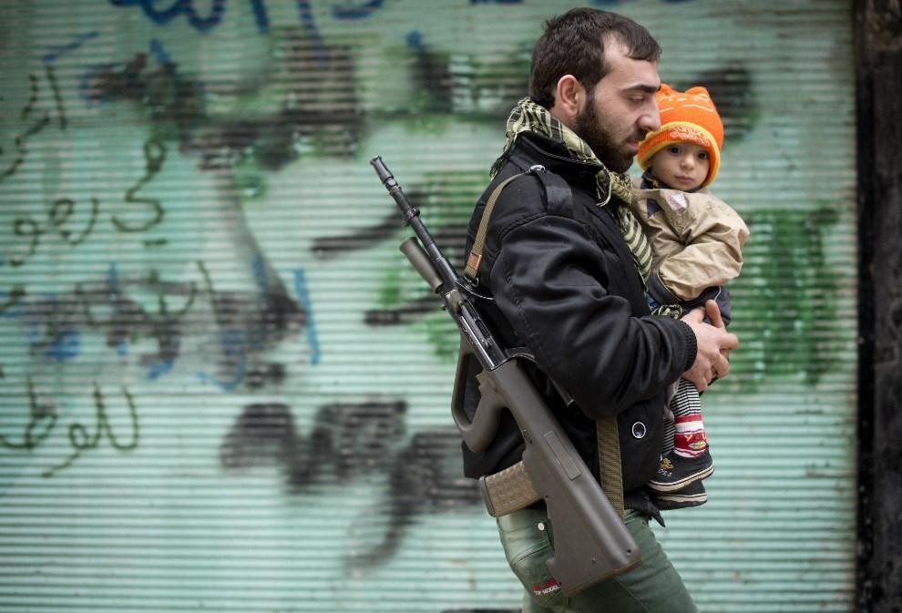 15.SYRIA, Aleppo, 7 grudnia 2012: Rebeliant z synem na rękach. AFP PHOTO / ODD ANDERSEN