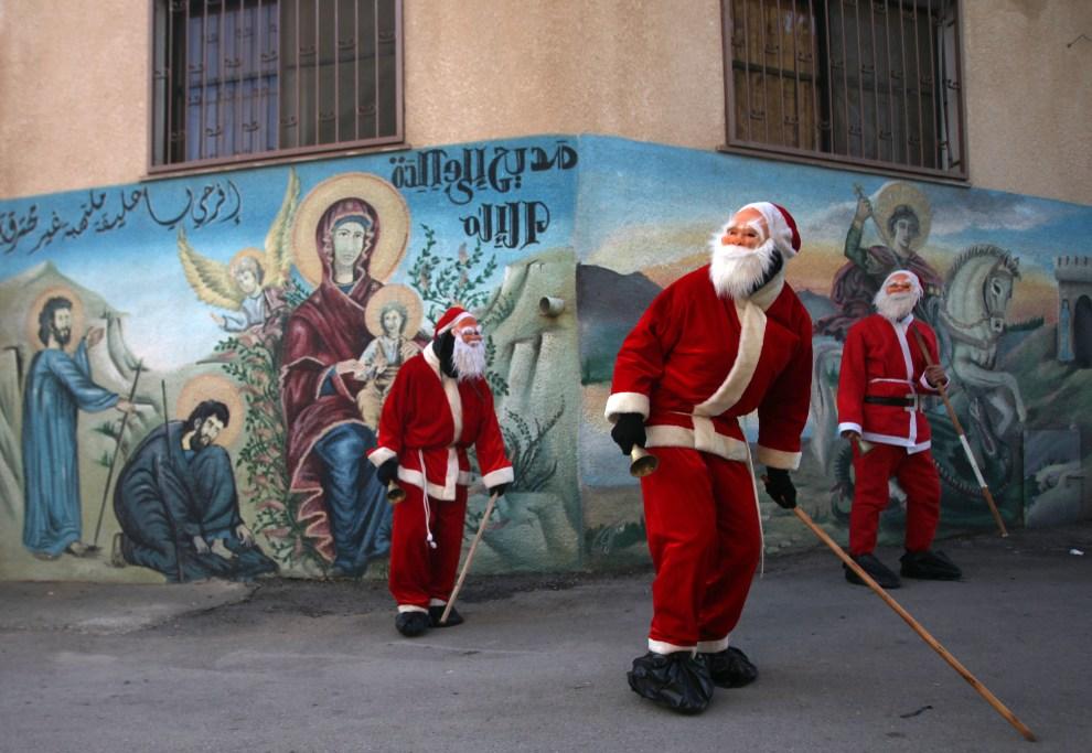 14.ZACHODNI BRZEG, 22 grudnia 2012: Mężczyźni w kostiumach Mikołaja przechadzają się po wiosce Abud, którą zamieszkują zarówno chrześcijanie jak i muzułmanie. AFP   PHOTO/ABBAS MOMANI