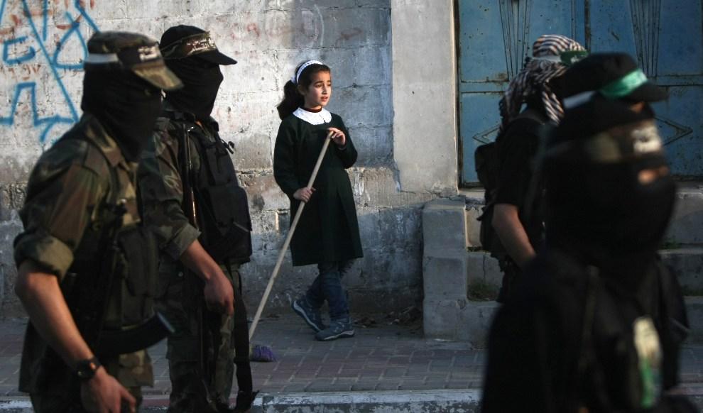 16.STREFA GAZY, 2 grudnia 2012: Dziewczynka przygląda się maszerującym bojownikom z ugrupowania Ezzedine al-Qassam. AFP PHOTO/MAHMUD HAMS
