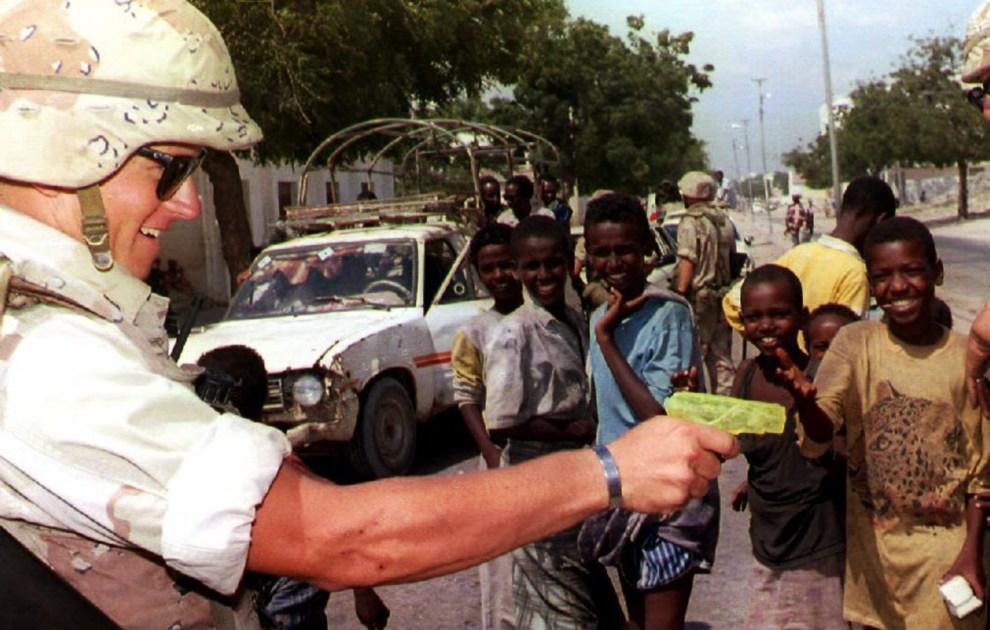 15.SOMALIA, Mogadiszu, 10 marca 1993: Amerykański żołnierz bawi się pistoletem na wodę. AFP PHOTO