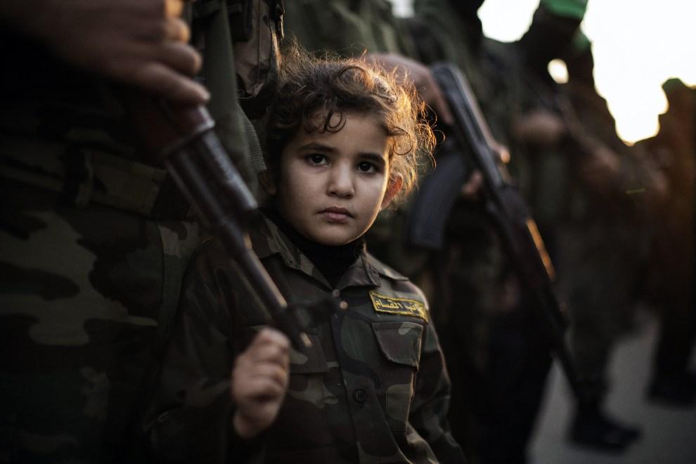 17.STREFA GAZY, Bajt Hanun, 6 grudnia 2012: Dziewczynka trzyma się lufy AK 47 jednego z bojowników brygady Ezzedine al-Qassam. AFP PHOTO/MARCO LONGARI