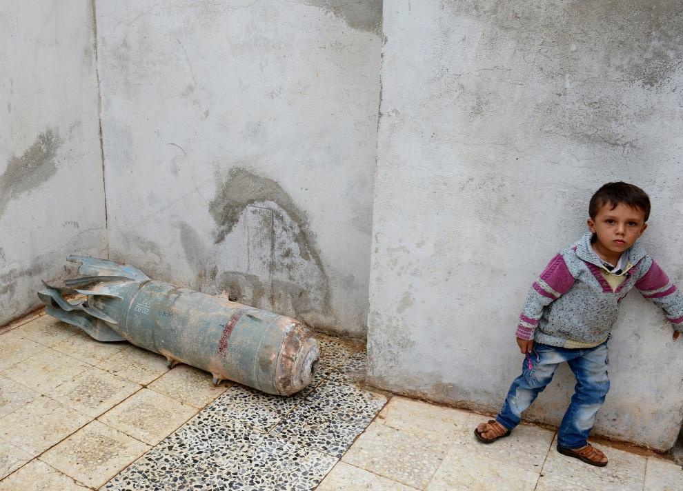 17. SYRIA, Taftanaz,9 listopada 2012: Dziecko stoi obok rozbrojonej bomby w pobliżu miejscowości Taftanaz. AFP PHOTO/PHILIPPE DESMAZES