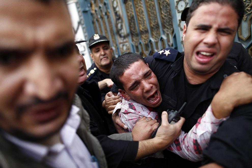 19.EGIPT, Kair, 5 grudnia 2012: Policjanci ochraniają opozycyjnego demonstranta po tym, jak został zaatakowany przez zwolenników Bractwa Muzułmańskiego. AFP   PHOTO/MAHMOUD KHALED