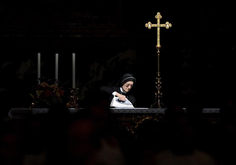 18.WATYKAN, 27 maja 2012: Zakonnica prasuje obrus przygotowując ołtarz do odprawienia mszy przez Benedykta XVI. AFP PHOTO/ FILIPPO MONTEFORTE