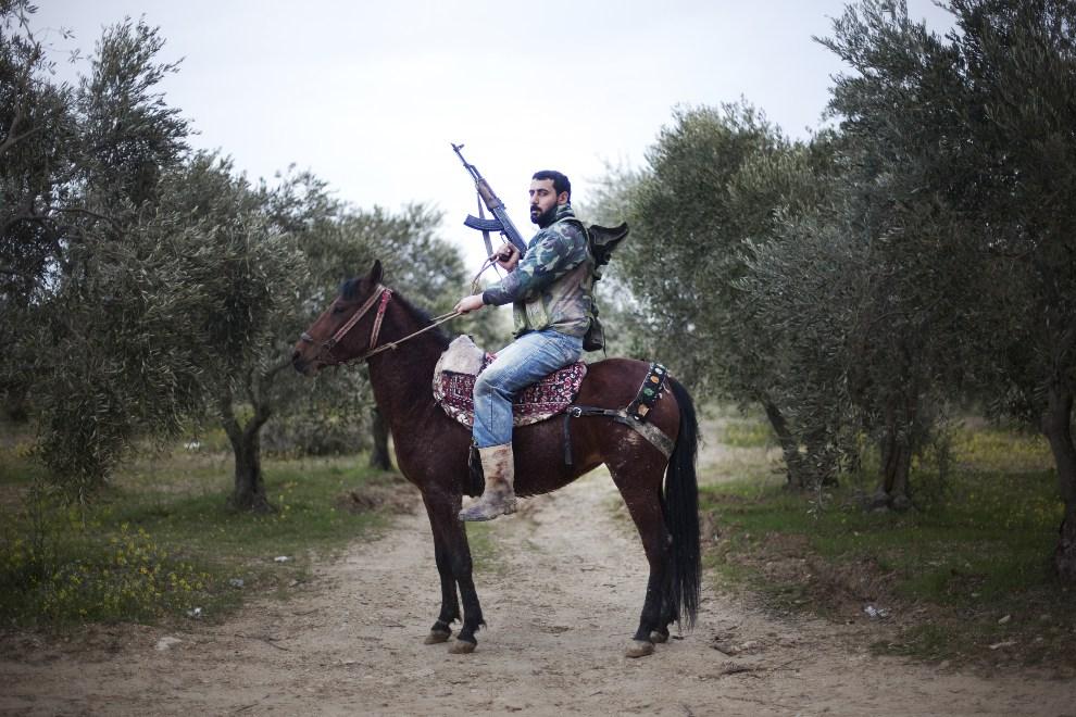 19.SYRIA, Al-Shatouria, 16 marca 2012: HATOURIA : Rebeliant z Wolnej Armii Syrii dosiadający konia. AFP PHOTO/GIOGOS MOUTAFIS
