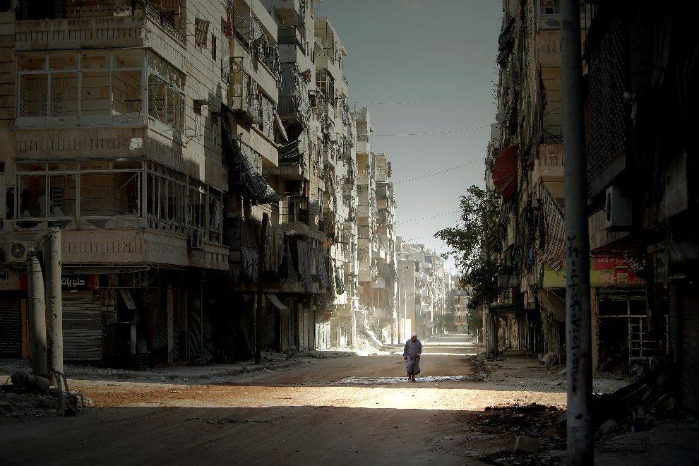 19.  SYRIA, Aleppo, 3 września 2012: Mężczyzna idący ulicą wśród ostrzelanych budynków. AFP PHOTO/JOSEPH EID