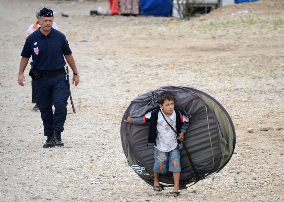 21.FRANCJA, Saint-Priest, 28 sierpnia 2012:  Romskie dziecko niosąc namiot na plecach, opuszcza obóz zlikwidowany przez policję. AFP PHOTO/PHILIPPE DESMAZES