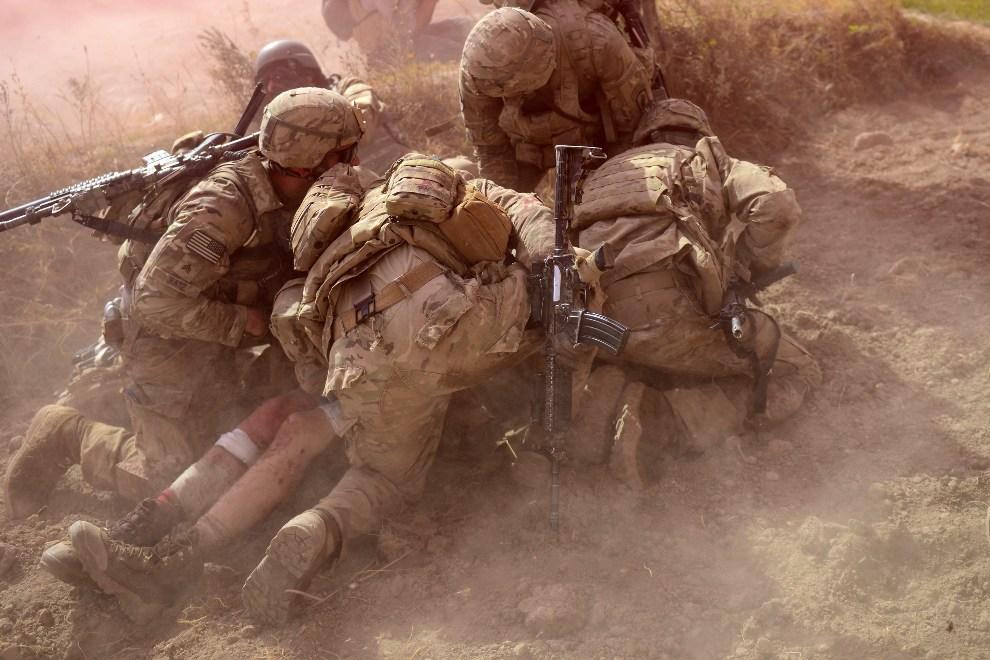 22. AFGANISTAN, Baraki Barak, 13 października 2012: Amerykańscy żołnierze osłaniają przed kurzem rannego towarzysza. AFP PHOTO/ Munir uz ZAMAN