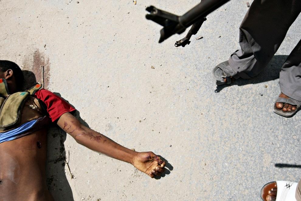 22.SOMALIA, Mogadiszu, 1 grudnia 2009: Żołnierz sił rządowych stoi obok ciała zabitego rebelianta. AFP PHOTO/MOHAMED DAHIR