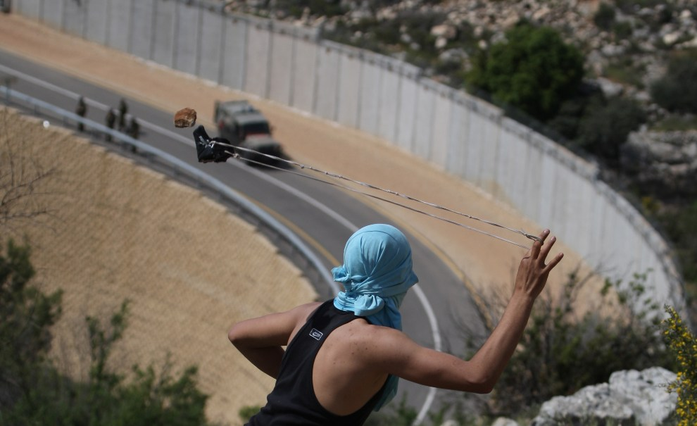 23.ZACHODNI BRZEG, 13 kwietnia 2012: Palestyńczyk z procą celujący w izraelskich żołnierzy. AFP PHOTO/ABBAS MOMANI