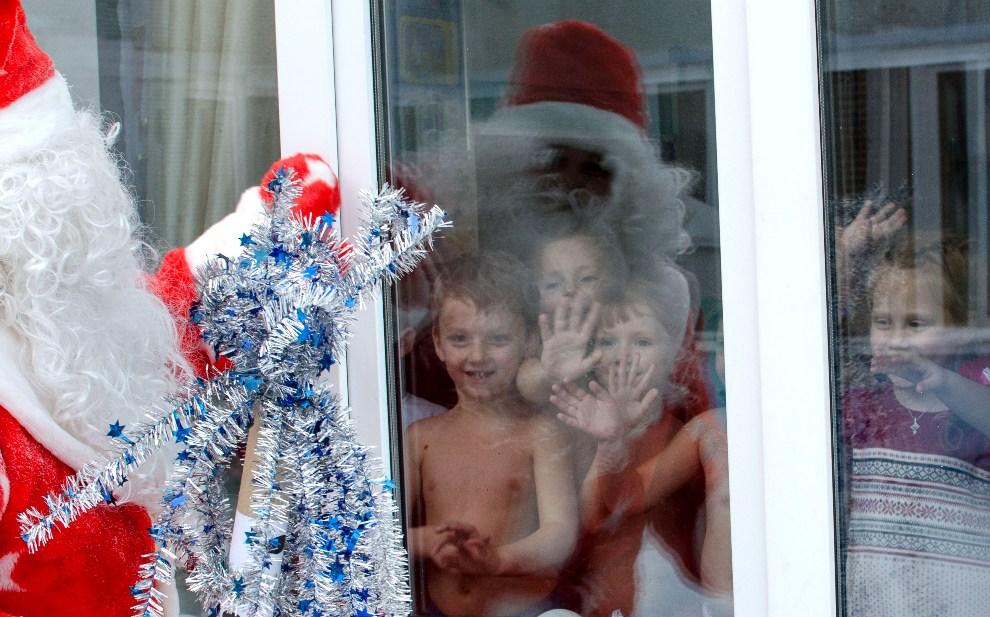 24.ROSJA, Nowosybirsk, 17 grudnia 2012: Dzieci pozdrawiają przez szybę Dziadka Mroza.  AFP PHOTO / VALERY TITIEVSKY