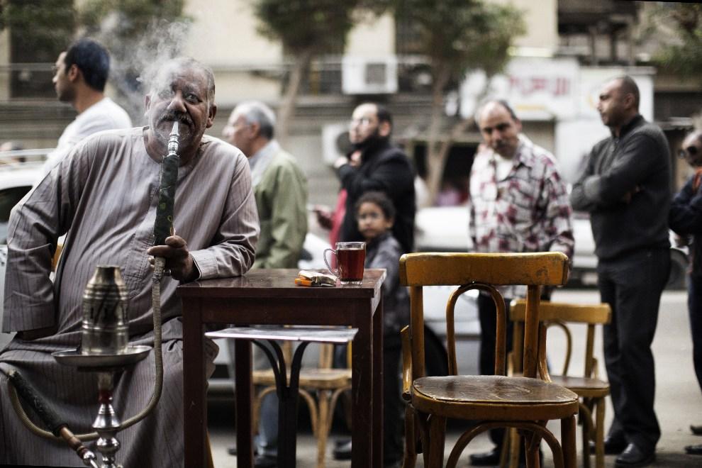 24.EGIPT, Kair, 15 grudnia 2012: Mężczyzna palący fajkę wodną przed lokalem wyborczym. AFP PHOTO/MARCO LONGARI