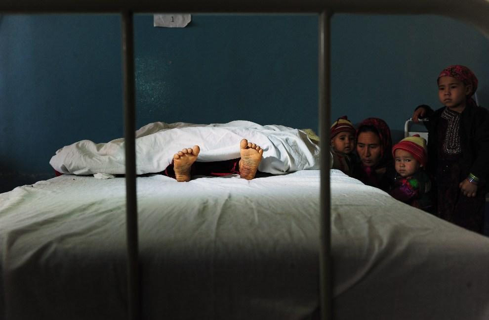25. AFGANISTAN, Mazar-i-Sharif, 12 listopada 2012: Rodzina zgwałconej pięcioletniej dziewczynki przy jej szpitalnym łóżku. AFP PHOTO/ Qais Usyan