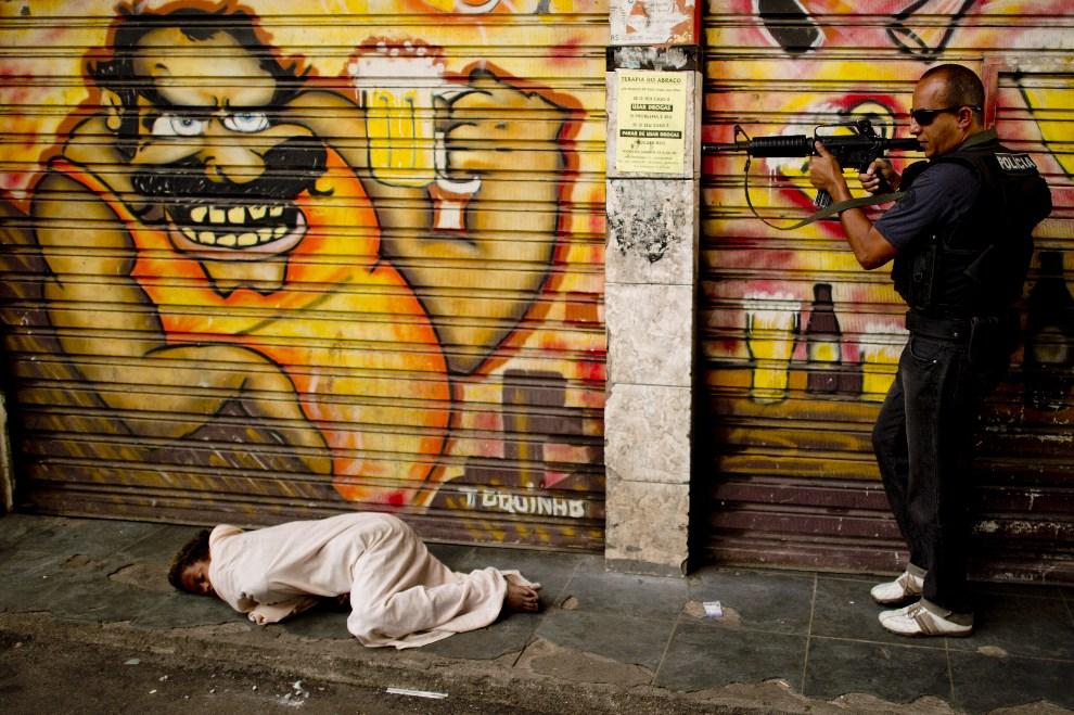 26. BRAZYLIA, Rio de Janeiro, 12 września 2012: Policjant zabezpiecza teren zanim podniesie śpiące na ulicy dziecko uzależnione od cracku. AFP PHOTO/Christophe Simon