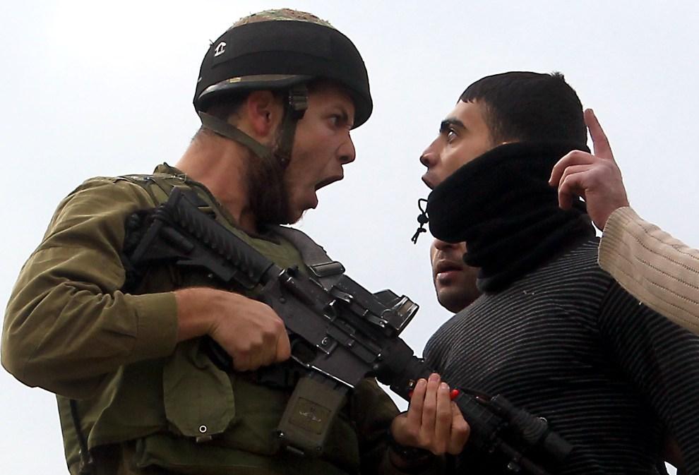 27.ZACHODNI BRZEG, 17 grudnia 2012: Palestyńczyk kłóci się z izraelskim żołnierzem. AFP PHOTO/JAAFAR ASHTIYEH