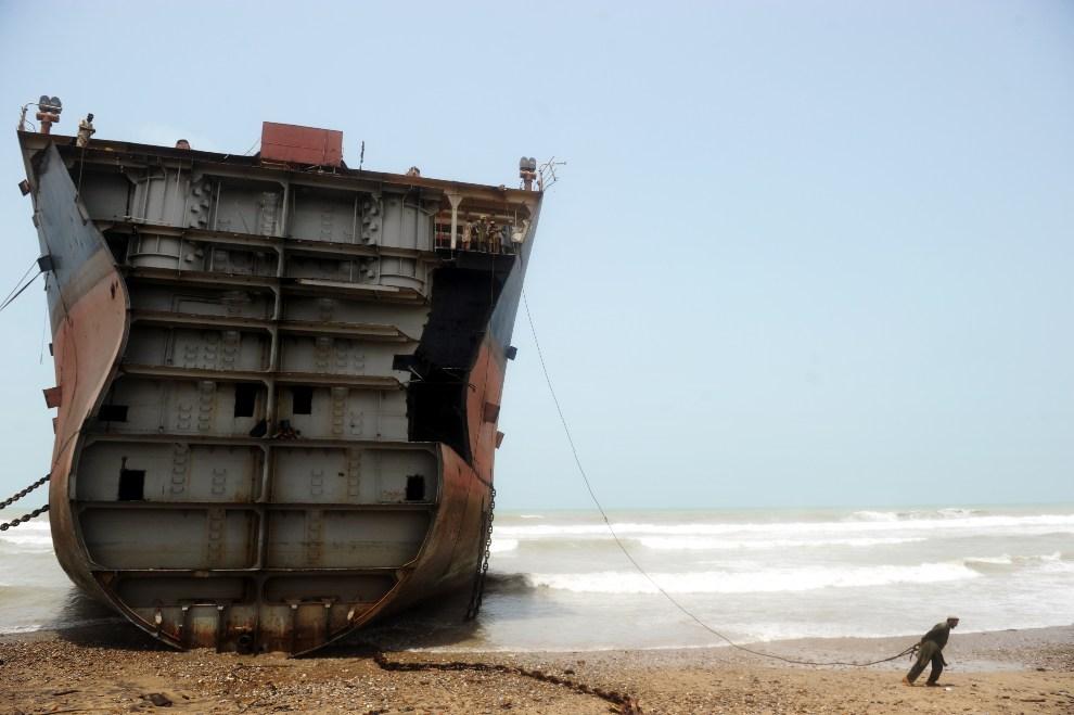 28.PAKISTAN, Geddani, 10 lipca 2012: Mężczyzna napina linę, którą chce oderwać fragment blachy ze złomowanego statku. AFP PHOTO / Roberto SCHMIDT