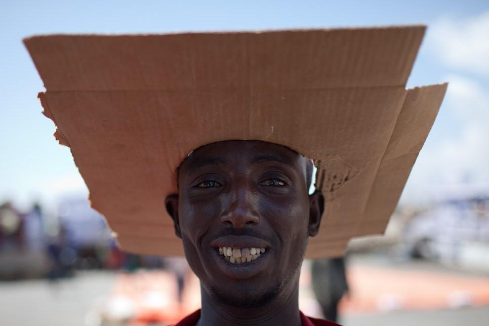 """28.SOMALIA, Mogadiszu, 24 listopada 2009: Pracownik portowy w """"czapce"""" z kartonu. AFP PHOTO / YASUYOSHI CHIBA"""
