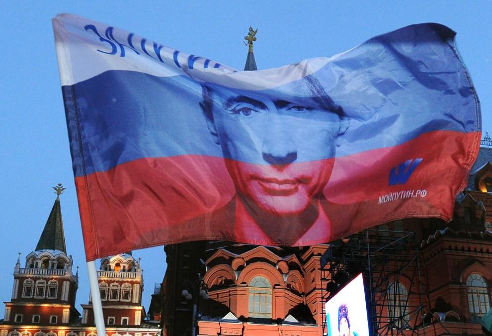 29.ROSJA, Moskwa, 5 marca 2012: Rosyjska flaga z wizerunkiem Władimira Putina powiewająca nad  Placem Maneżowym. AFP PHOTO / ALEXANDER NEMENOV
