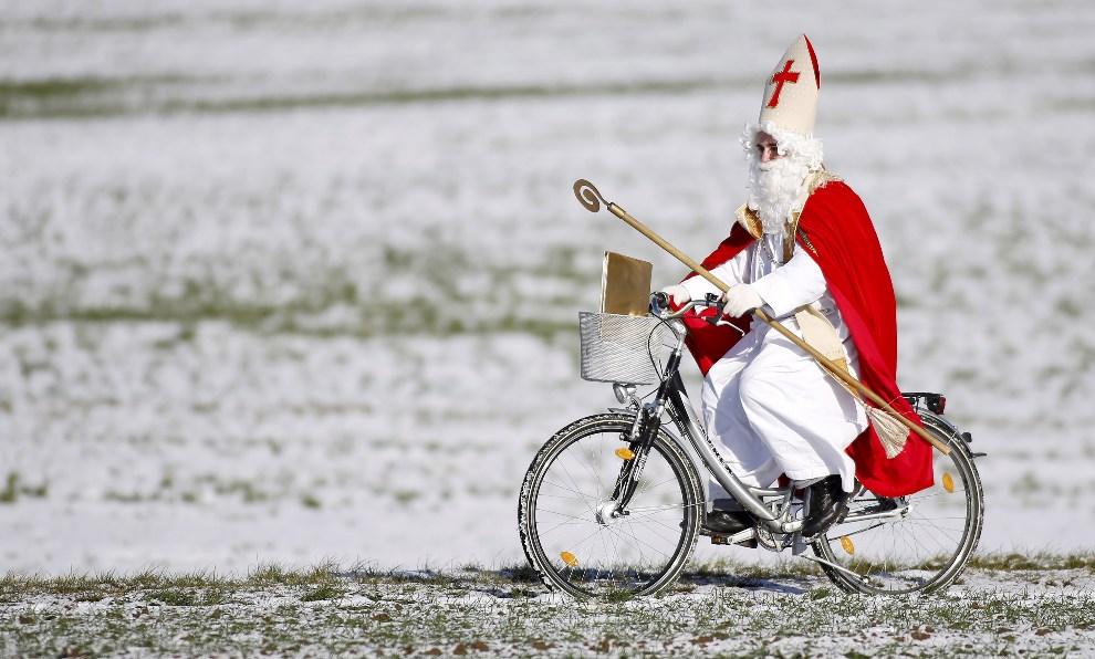 2.NIEMCY, Offingen, 6 grudnia 2012: Mężczyzna w stroju Mikołaja jedzie na rowerze. AFP PHOTO / THOMAS WARNACK