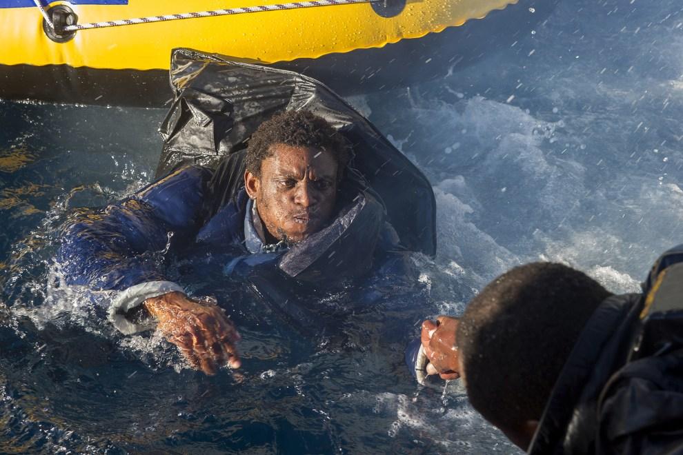 30. NA MORZU, 3 grudnia 2012: Imigrant wciągany na pokład łodzi straży przybrzeżnej u wybrzeży Hiszpanii. AFP PHOTO / MARCOS MORENO