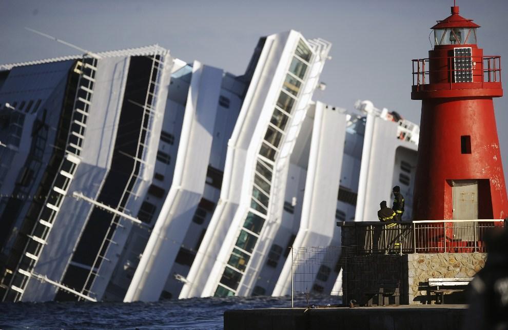 31.WŁOCHY, Isola del Giglio, 17 stycznia 2012: Strażacy przyglądają się zatopionemu liniowcowi Costa Concordia. AFP PHOTO / FILIPPO MONTEFORTE