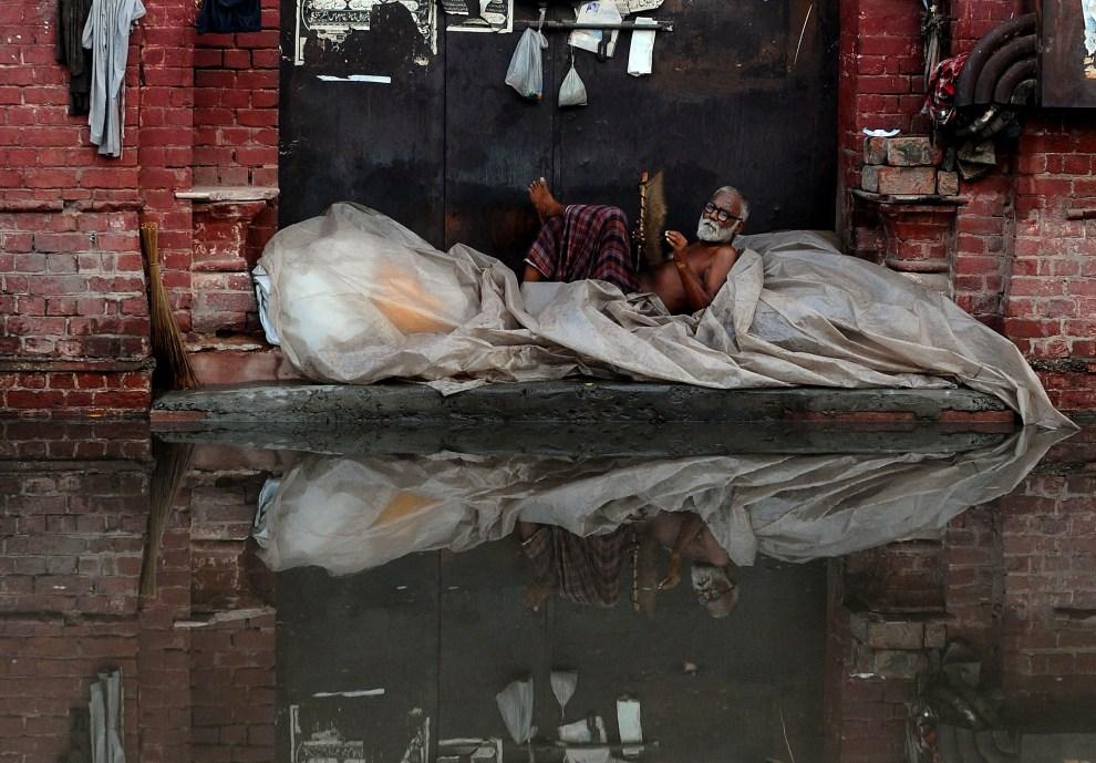 31.PAKISTAN, Lahore, 22 lipca 2012: Bezdomny chroni się przed wodą zalewająca ulice Lahore. AFP PHOTO/Arif ALI