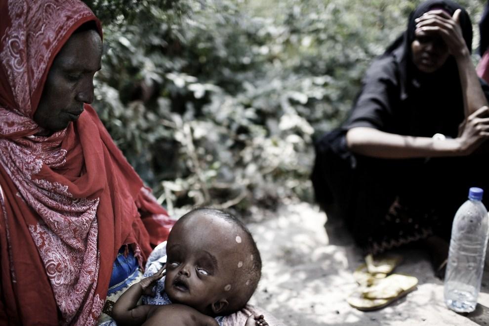 32.SOMALIA, Mogadiszu, 9 grudnia 2007: Kobieta z chorym dzieckiem czeka przed wejściem do szpitala. AFP PHOTO/JOSE CENDON
