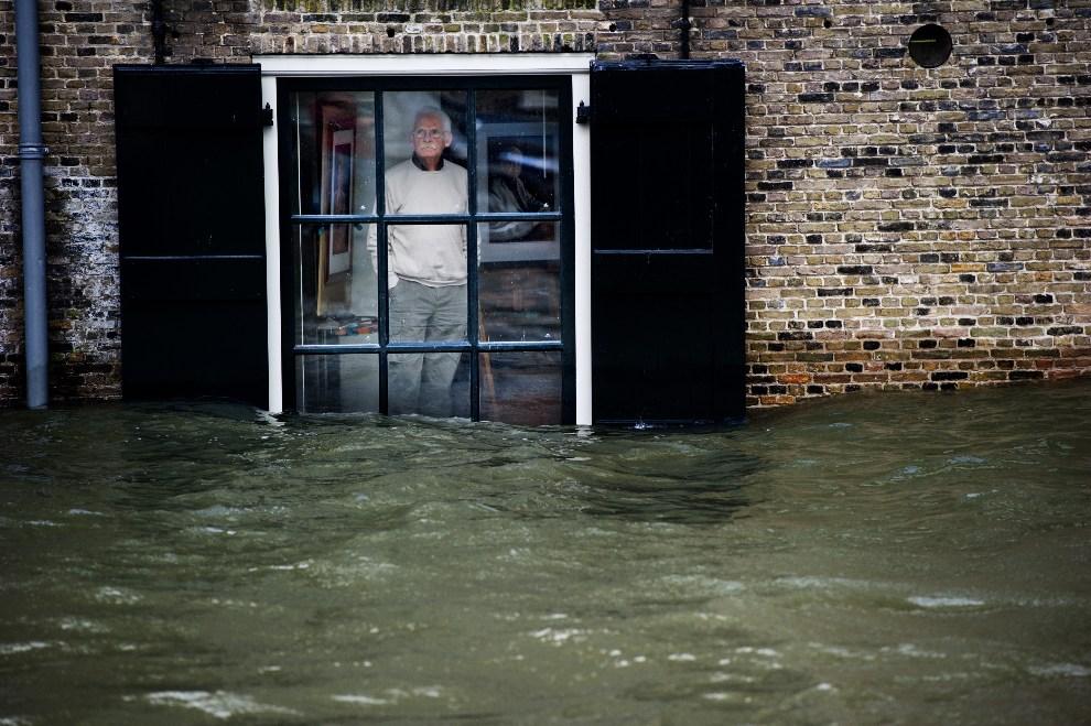 32.HOLANDIA, Dordrecht, 5 stycznia 2012: Mężczyzna przygląda się opadającej wodzie podczas powodzi  na wybrzeżu Holandii. AFP PHOTO / ANP / ROBIN UTRECHT