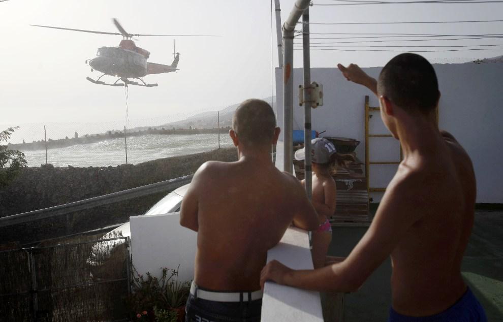 32.HISZPANIA, Teneryfa, 19 lipca 2012: Helikopter nabiera wodę z basenu przy jednym z domów na Teneryfie. AFP PHOTO/Desiree Martin