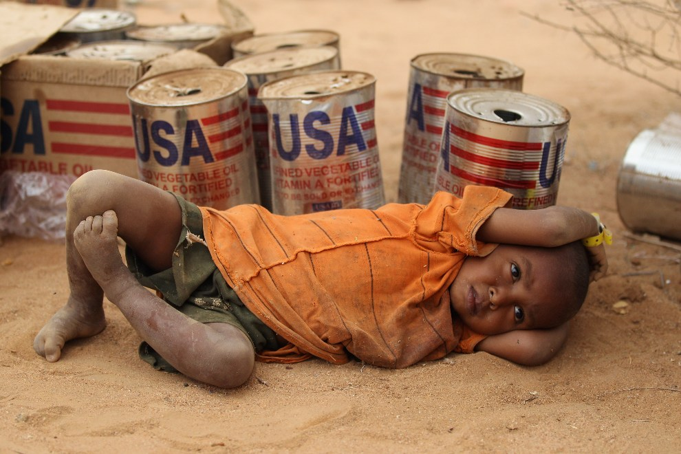 35.KENIA, Dadaab, 19 lipca 2011: Mały chłopiec odpoczywa na tle pustych puszek po żywności. (Foto:Oli Scarff/Getty Images)