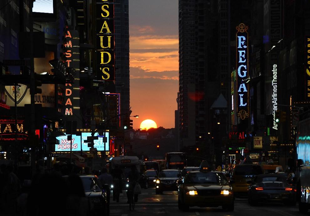36.USA, New York, 11 lipca 2012: Zachód słońca nazywany Manhattanhenge, obserwowany dwa razy do roku, kiedy zachodzące słońce idealnie równa się z kierunkiem   zachodnich i wschodnich ulic Manhattanu. AFP PHOTO / TIMOTHY A. CLARY
