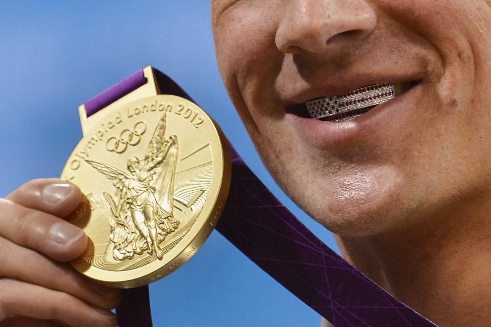 3.WIELKA BRYTANIA, Londyn, 28 lipca 2012: Amerykanin Ryan Lochte pozuje do zdjęcia po zdobyciu złotego medalu. AFP PHOTO / FABRICE COFFRINI