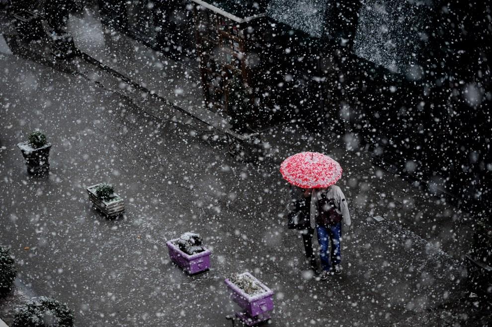 6.SERBIA, Prisztina, 5 grudnia 2012: Para młodych ludzi chroni się pod parasolem przed śniegiem. AFP PHOTO/ARMEND NIMANI