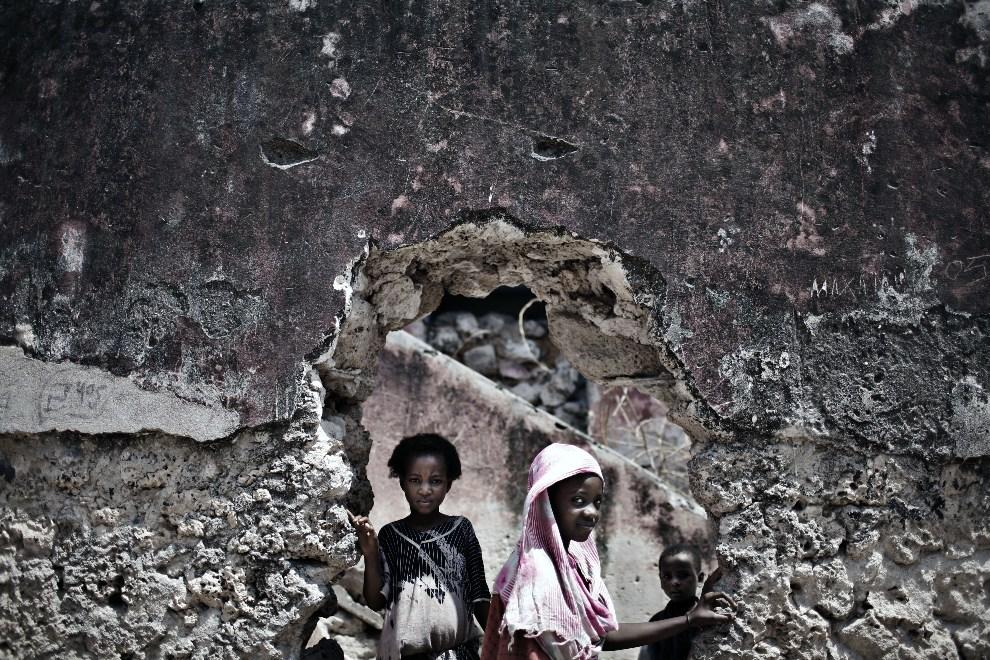 7.SOMALIA, Mogadiszu, 8 grudnia 2007: Dziewczynki wyglądają przez wybitą w murze dziurę. AFP PHOTO/JOSE CENDON