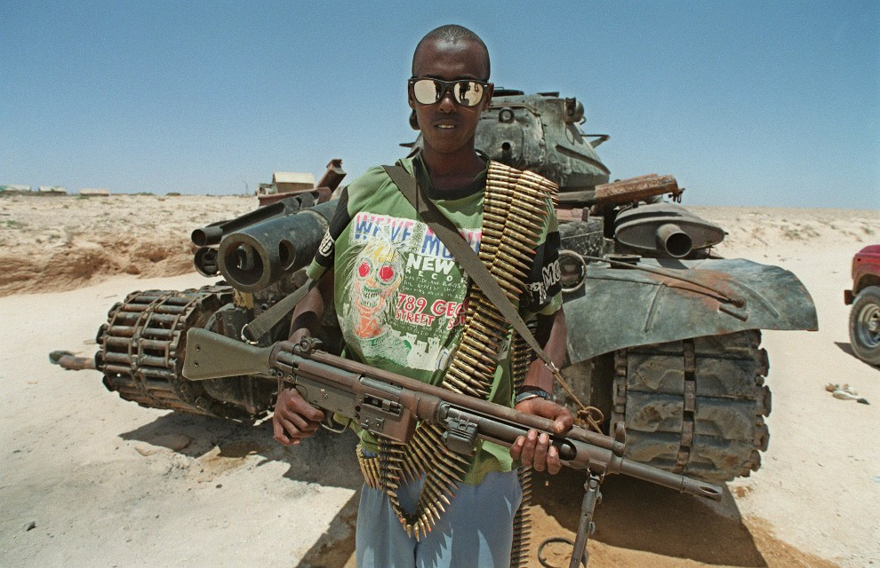 9.SOMALIA, Mogadiszu, 26 lutego 1992: Bojownik z oddziału wiernego  Alemu Mahdi Mohamedowi pozuje na tle spalonego  T-54. AFP PHOTO ALEXANDER JOE