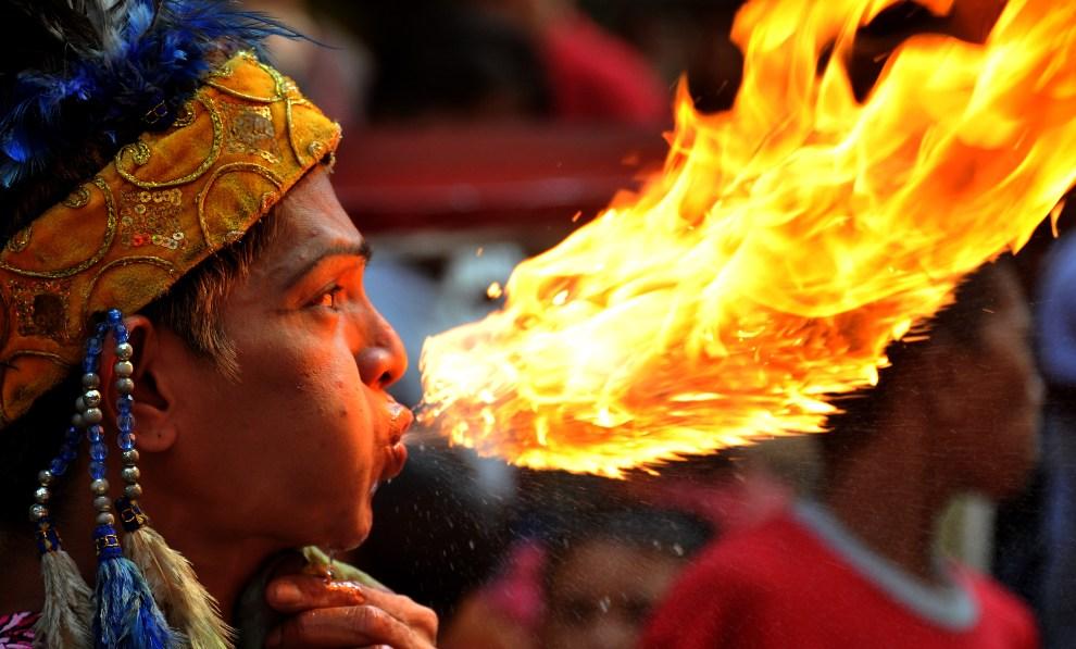 9.FILIPINY, Manila, 22 stycznia 2012: Mężczyzna ziejący ogniem podczas noworocznej zabawy. AFP PHOTO/NOEL CELIS